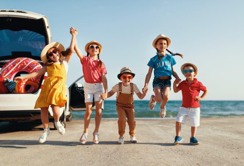 Meisjes van groeps berijden de gelukkige kinderen en de jongensvrienden op auto aan de zomerreis royalty-vrije stock afbeelding