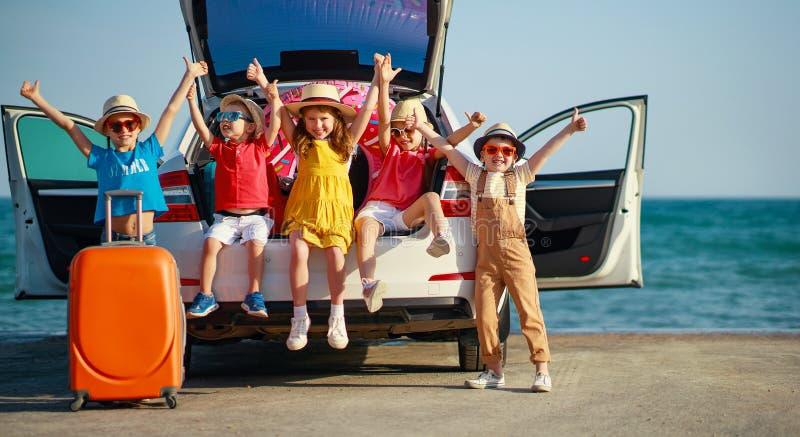 Meisjes van groeps berijden de gelukkige kinderen en de jongensvrienden op auto aan de zomerreis stock fotografie