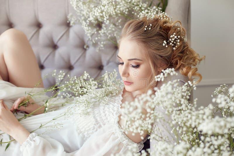 Meisjes witte lichte kleding en krullend haar, portret van vrouw met bloemen thuis dichtbij het venster, zuiverheid en onschuld K stock foto's