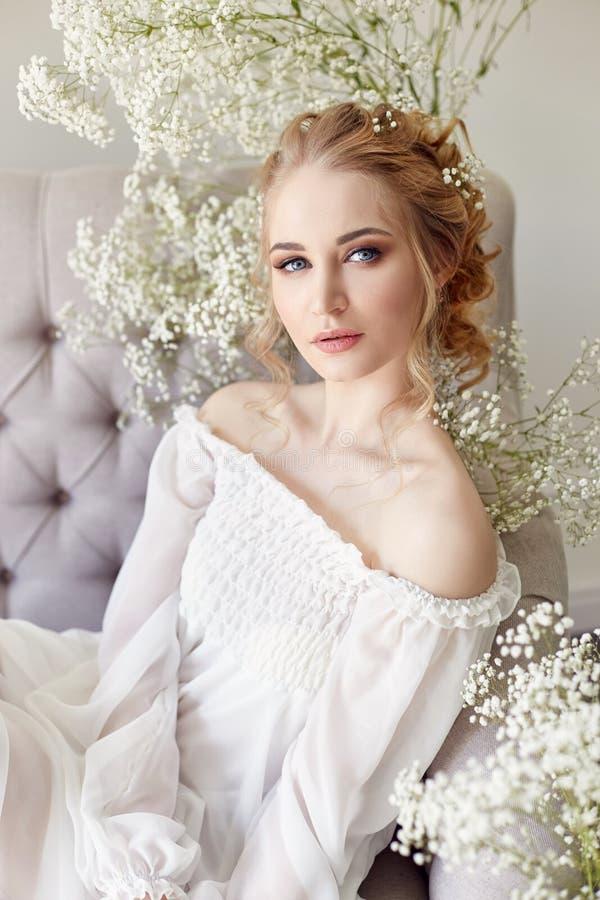 Meisjes witte lichte kleding en krullend haar, portret van vrouw met bloemen thuis dichtbij het venster, zuiverheid en onschuld K royalty-vrije stock foto's
