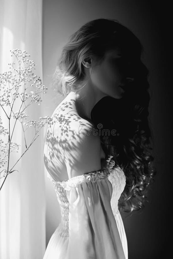 Meisjes witte lichte kleding en krullend haar, portret van vrouw met bloemen thuis dichtbij venster, zuiverheid en onschuld Krull stock afbeelding