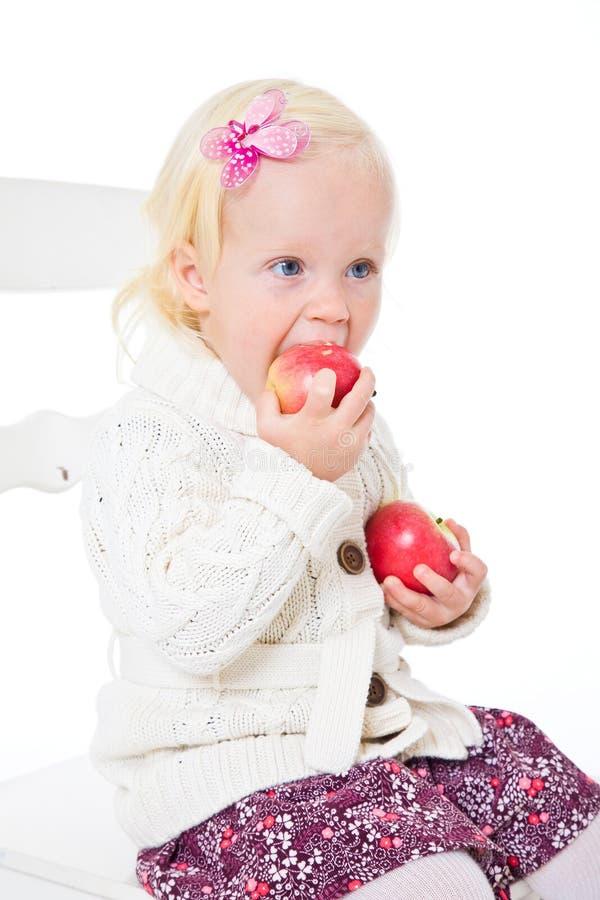 meisjes zitting op een stoel met rode appelen royalty-vrije stock foto
