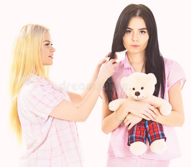 Meisjesachtig vrije tijdsconcept Zusters, beste vrienden die in pyjama's vlecht, kapsel maken elkaar Dames op het glimlachen gezi royalty-vrije stock afbeeldingen