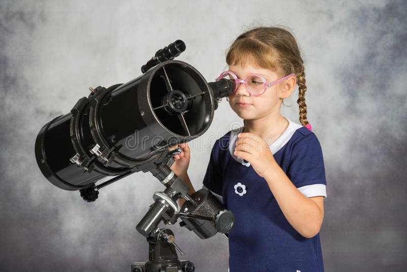 Meisjesastronoom gelukkig wordt verrast door wat hij in de telescoop die zag stock fotografie