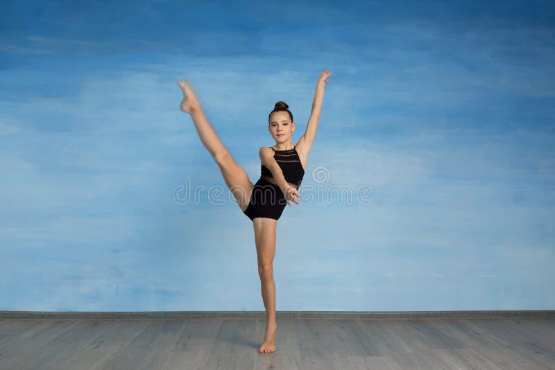 Meisjesatleet die oefeningsgymnastiek doen, die de camera bekijken stock foto