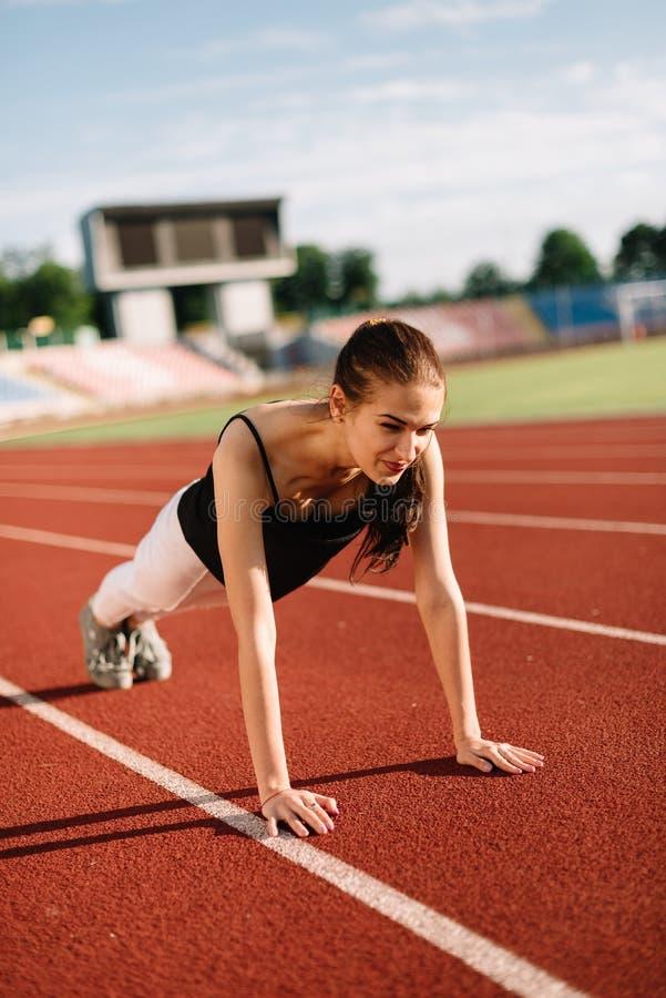Meisjesatleet op het gebied op een zonnige dag uit wordt gewrongen die royalty-vrije stock fotografie