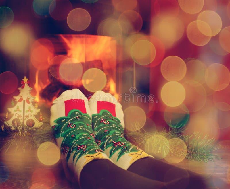 Meisjesbenen in sokken dichtbij de open haard met wat Kerstmisboom royalty-vrije stock afbeeldingen