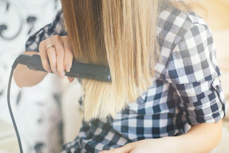 Meisjesbezinning in de spiegel, die de haarkapper maakt , het lichte stemmen stock foto