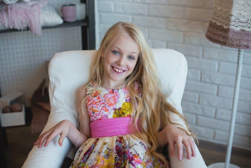 Meisjesblonde met lange haarzitting als voorzitter en het glimlachen, decoratie, decor, levensstijl, familie, familiewaarden stock foto