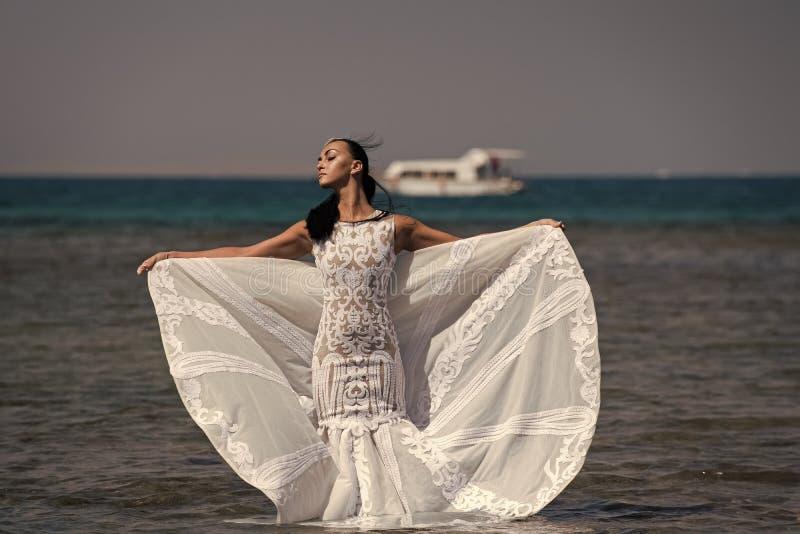 Meisjesbruid het stellen in huwelijkskleding met schip in overzees royalty-vrije stock afbeelding