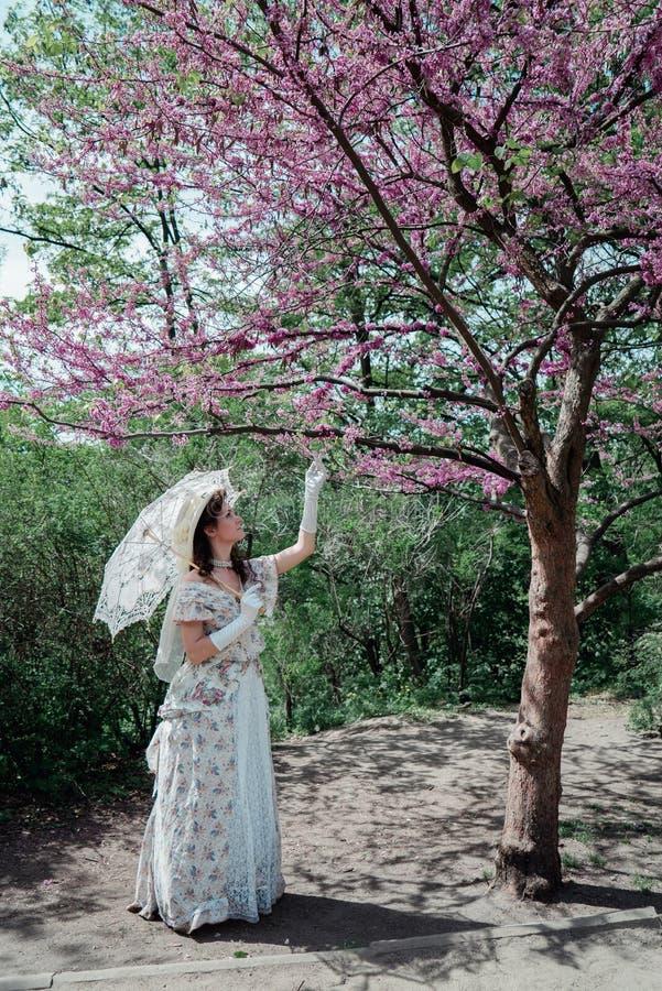 Meisjesbruid in uitstekende kleding die dichtbij boom bloeien stock foto