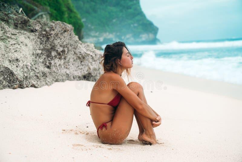 Meisjesbrunette met krullend haar in een rode bikini op het strand met wit zand dichtbij de oceaan op vakantie Een mooi model stock foto