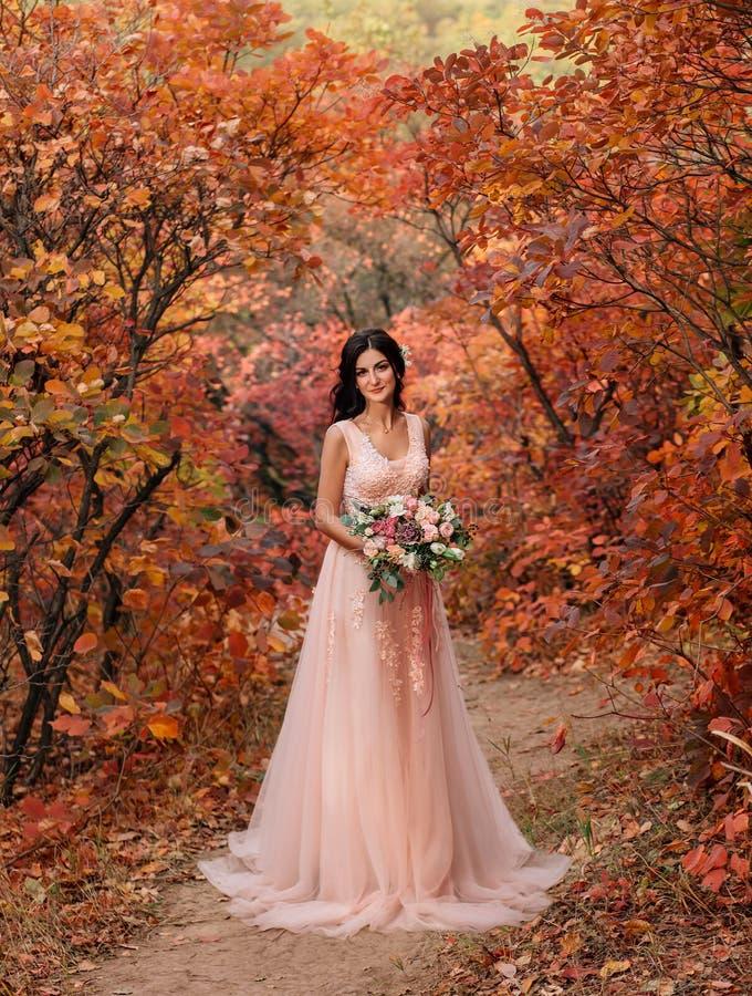 Meisjesbrunette met lang haar, in een luxueuze roze kleding met een lange trein De bruid met een boeket stelt tegen a royalty-vrije stock foto's