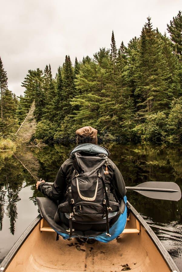 Meisjescanoeing met Kano op het meer van twee rivieren in het algonquin nationale park in Ontario Canada op bewolkte dag stock foto's