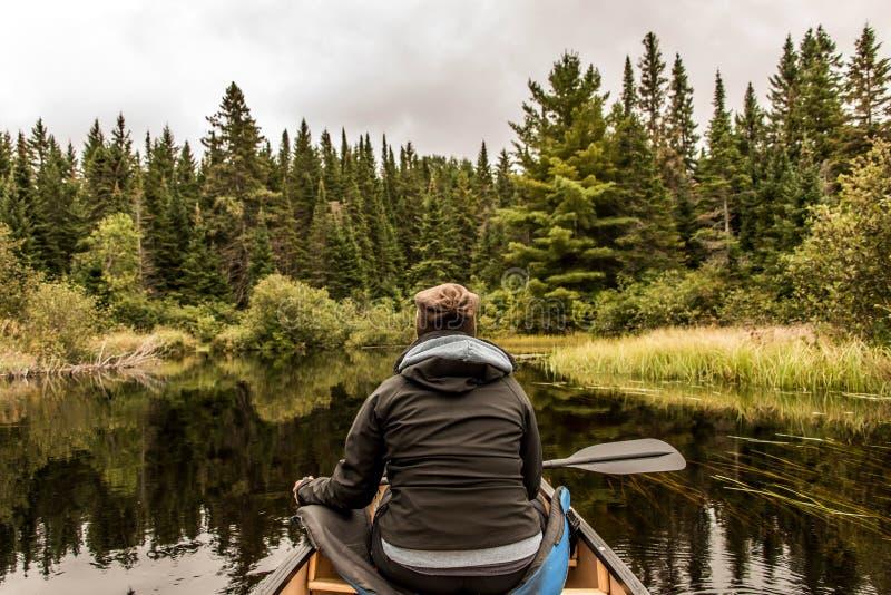 Meisjescanoeing met Kano op het meer van twee rivieren in het algonquin nationale park in Ontario Canada op bewolkte dag stock afbeeldingen