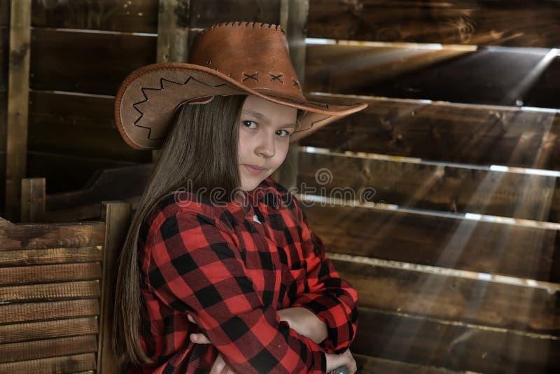 Meisjescowboy in een rood geruit overhemd op de achtergrond van een hout stock afbeelding