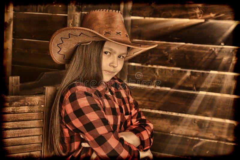 Meisjescowboy in een rood geruit overhemd op de achtergrond van een hout stock afbeeldingen