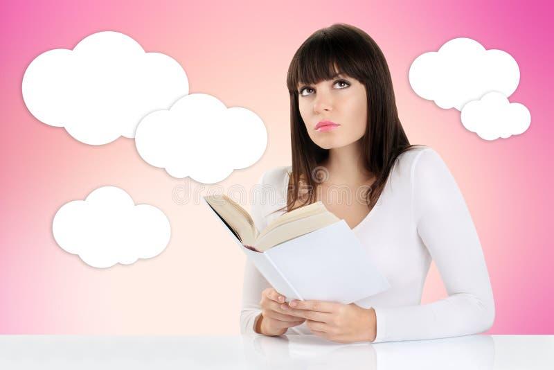 Meisjesdagdromen terwijl het lezen van een boek en het kijken omhoog op een roze royalty-vrije stock fotografie