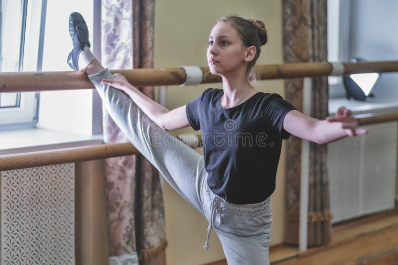 Meisjesdanser die oefeningen in de dansklasse doen bij de bank royalty-vrije stock afbeelding