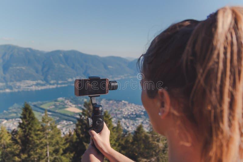 Meisjesfilm met gimbal in de bergen over meer maggiore royalty-vrije stock afbeeldingen