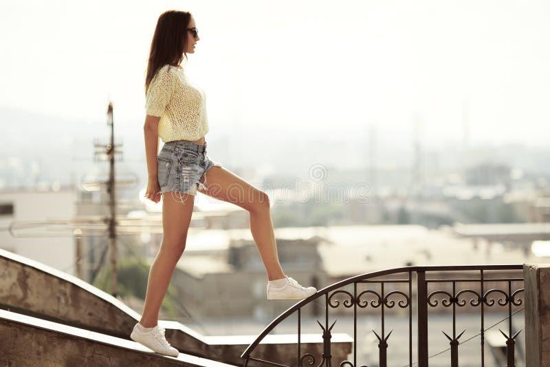 Meisjesgangen op het dak Stad bij achtergrond stock afbeelding