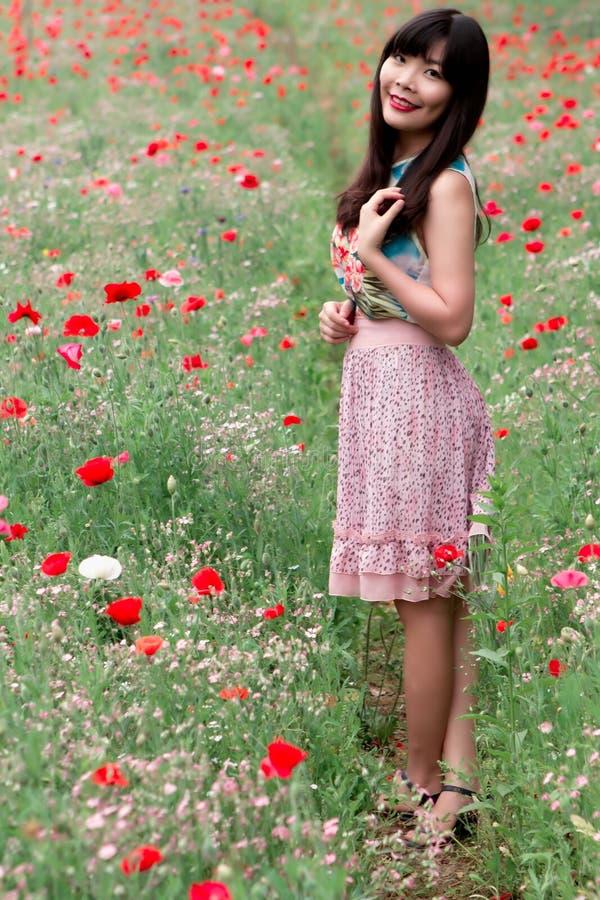 Meisjesglimlach met u op papavergebied royalty-vrije stock fotografie
