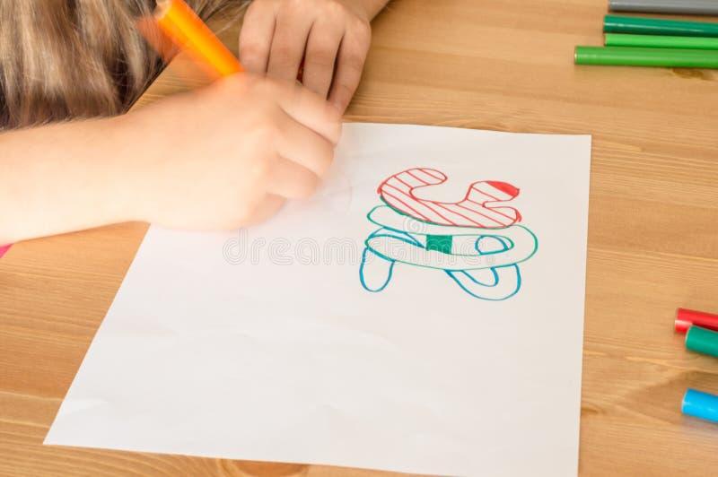 Meisjeshand het schrijven de Zomervakantie in Turks die kleurrijke viltpen gebruiken terwijl het zitten bij lijst in klaslokaal stock foto's