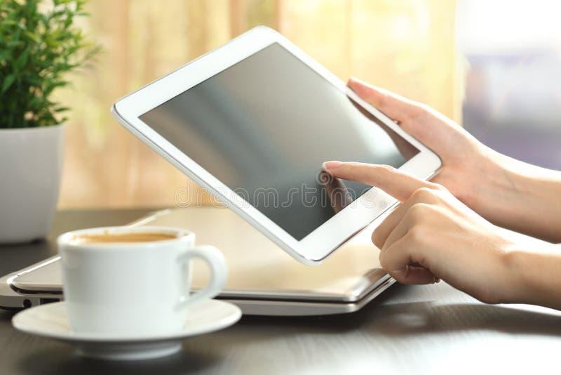 Meisjeshanden die een tablet thuis gebruiken stock foto