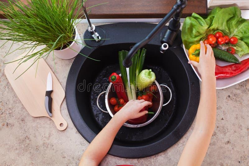 Meisjeshanden die groenten voor een gezonde salade wassen stock afbeeldingen