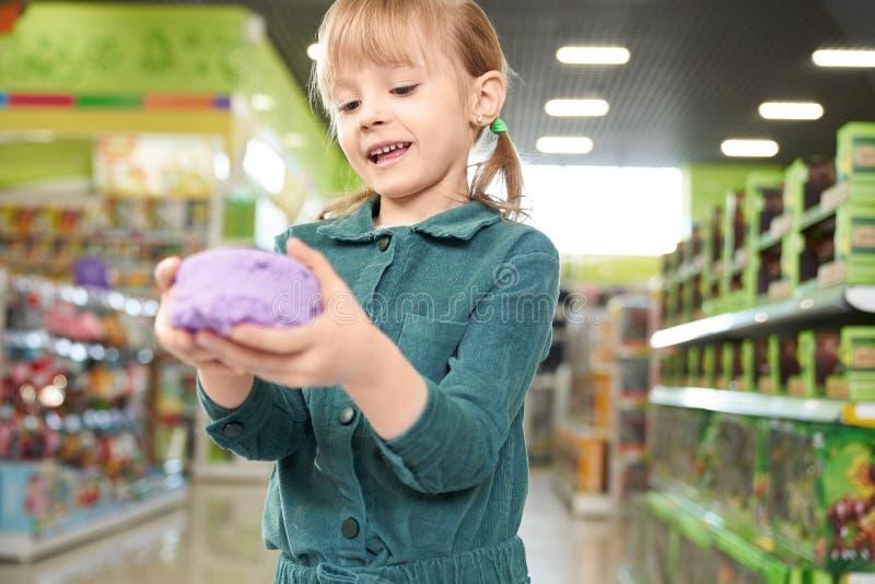 Meisjesholding in handen violet kinetisch zand, die bij camera stellen royalty-vrije stock foto's