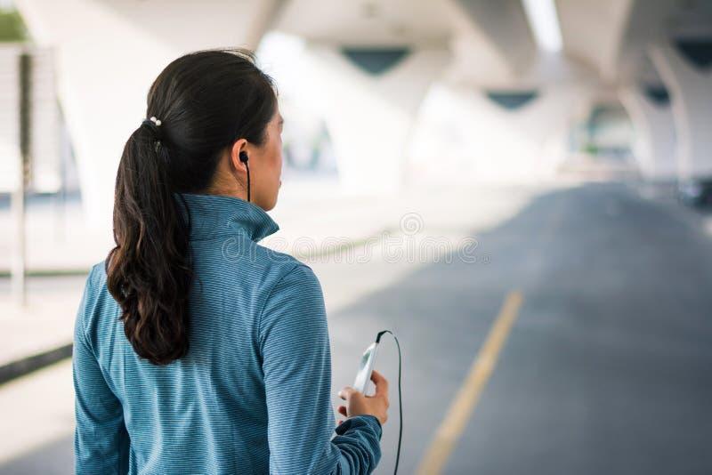 Meisjesjogging met oortelefoons en het luisteren aan muziek royalty-vrije stock foto's