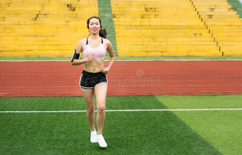 Meisjesjogging met smartphone op voetbalgebied stock foto's