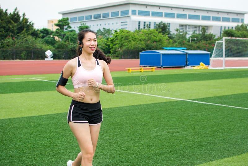 Meisjesjogging met smartphone op voetbalgebied stock fotografie
