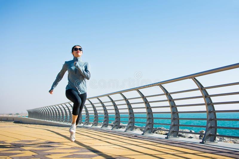 Meisjesjogging op de promenade door het overzees stock afbeeldingen