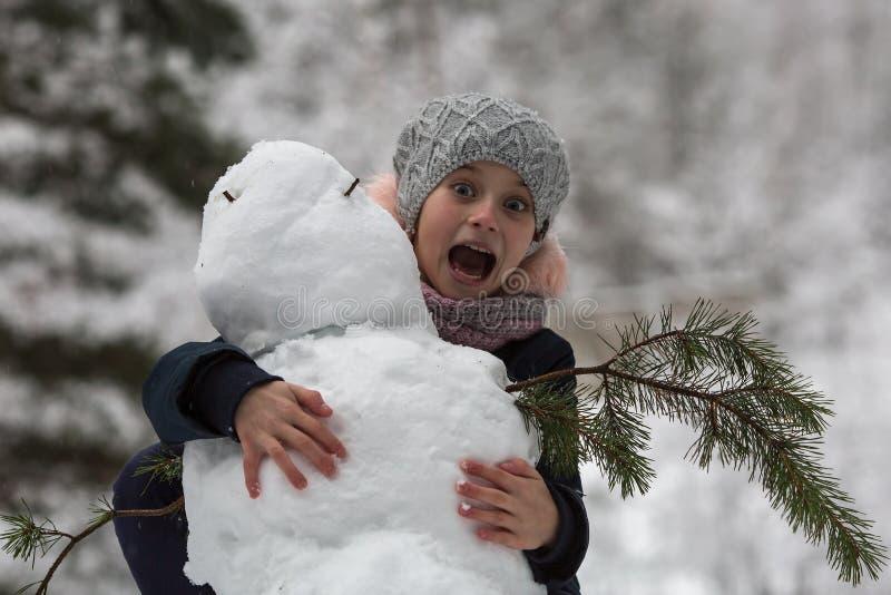 Meisjeskind en een sneeuwman De winter stock fotografie