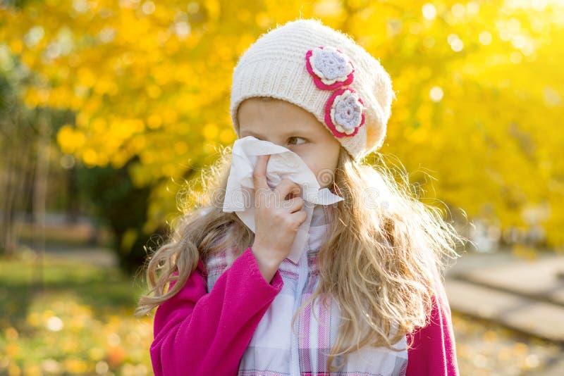 Meisjeskind met koud Rhinitis op de herfstachtergrond stock foto