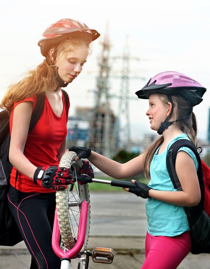 Meisjeskinderen die Familiepomp op fietsband cirkelen stock afbeeldingen