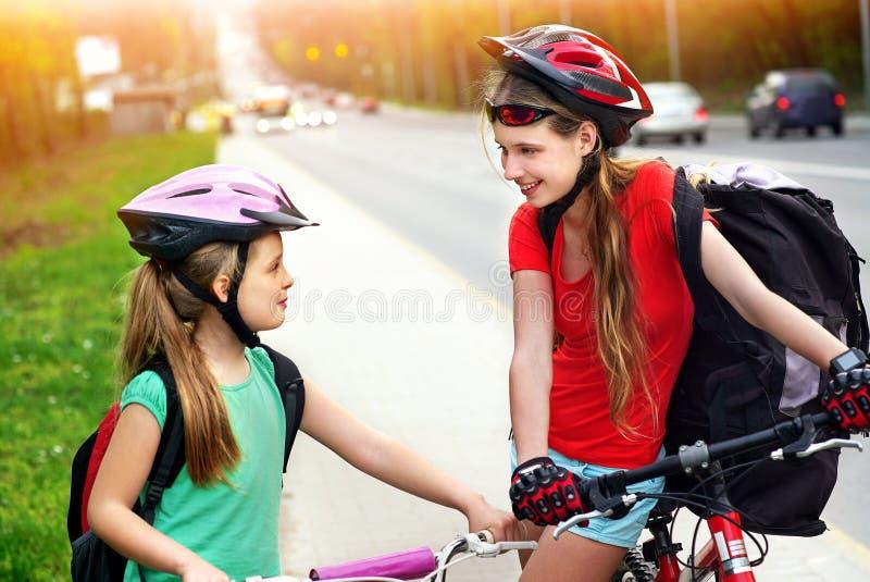 Meisjeskinderen die op gele fietssteeg cirkelen Er zijn auto's op weg stock fotografie
