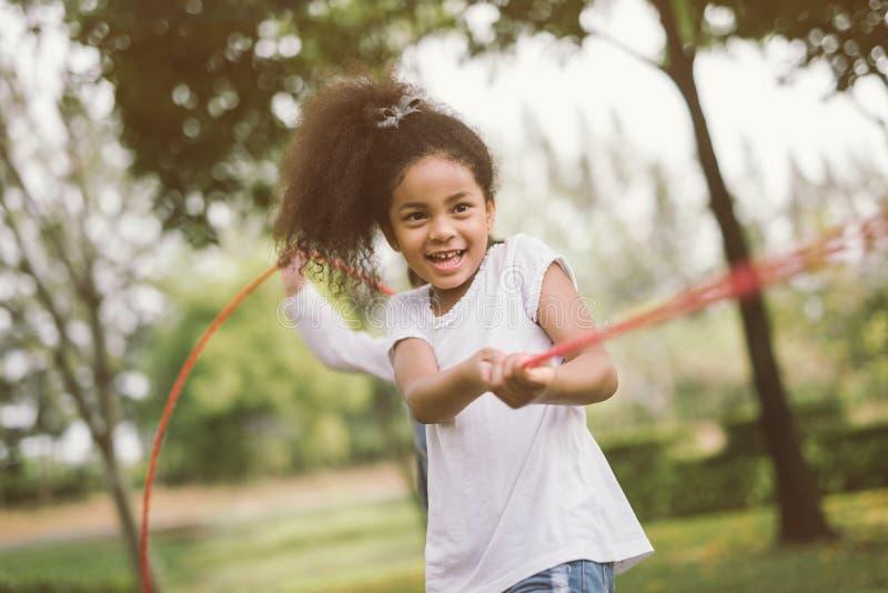 Meisjeskinderen die touwtrekwedstrijd spelen bij het park royalty-vrije stock afbeeldingen