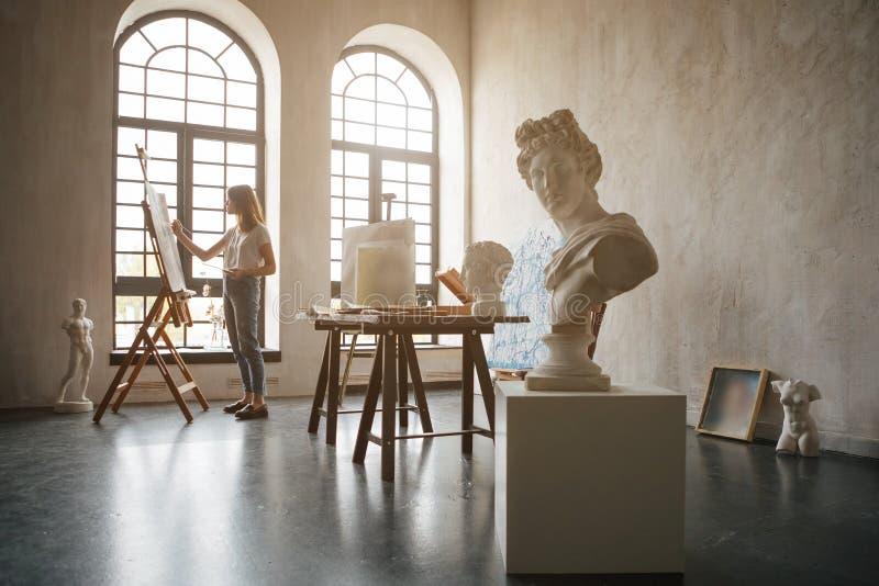 Meisjeskunstenaar die in de workshop lichte ruimte werken Het creëren van een beeld Het werk met verven, borstels en schilderseze stock foto