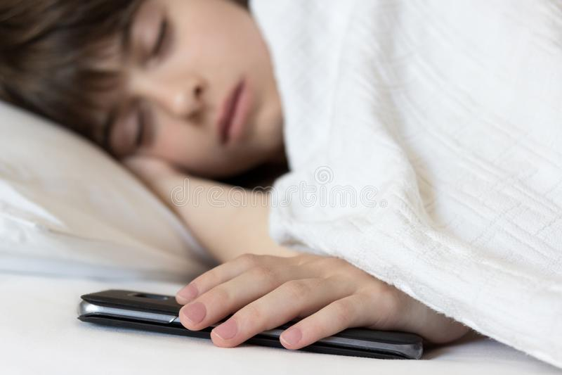 Meisjeslaap in het bed die haar cellphone houden Probleem van stock foto's