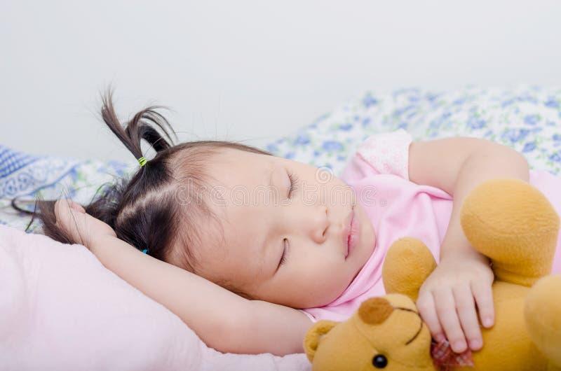 Meisjeslaap op bed stock afbeeldingen