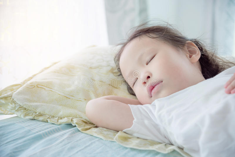 Meisjeslaap op bed royalty-vrije stock afbeeldingen