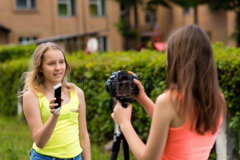 2 meisjesmeisje in de zomer in een park op aard Registreert de video op de camera, spreekt over de nieuwe telefoon Het concept royalty-vrije stock afbeelding