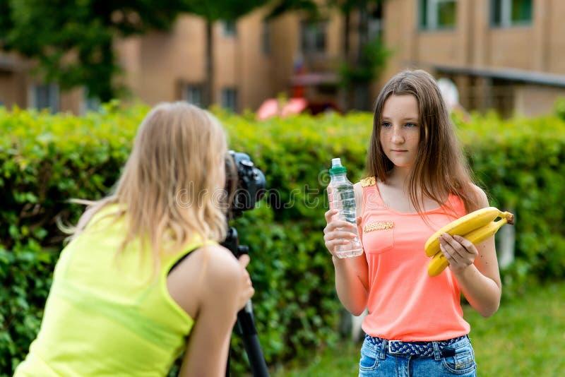 Meisjesmeisjes Vertelt over gezonde voeding Hij houdt nuttig fruit in zijn handen Een flessen zuiver water Verslag vlog royalty-vrije stock afbeelding