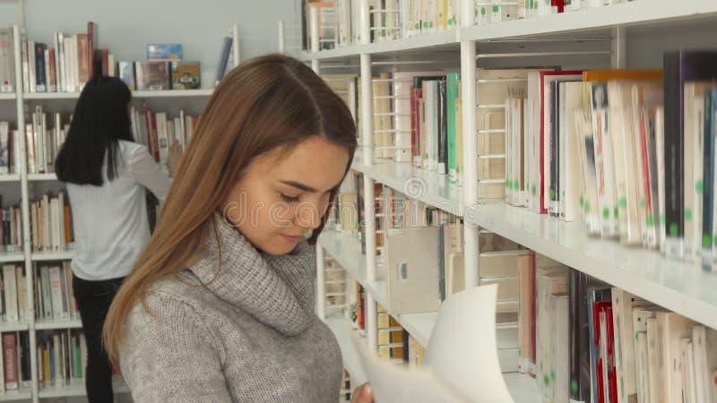 Meisjesonderzoeken naar het boek bij de bibliotheek royalty-vrije stock afbeeldingen