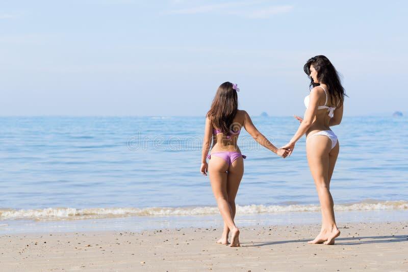 Meisjespaar op de Vakantie van de Strandzomer, Jonge Vrouw het Lopen Holdingshanden royalty-vrije stock afbeelding