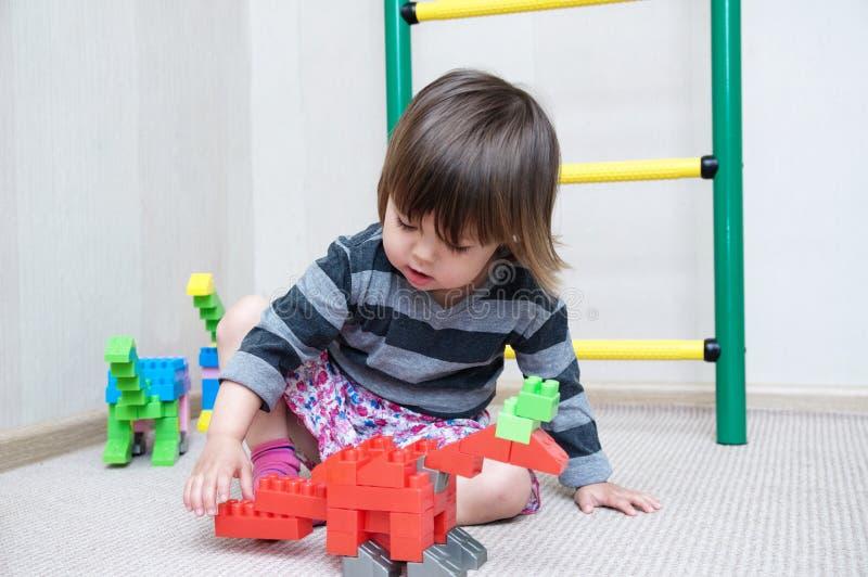 Meisjespel met dinosaurusbeeldjes door het plastic speelgoed dat van het aannemersblok wordt gemaakt royalty-vrije stock foto's