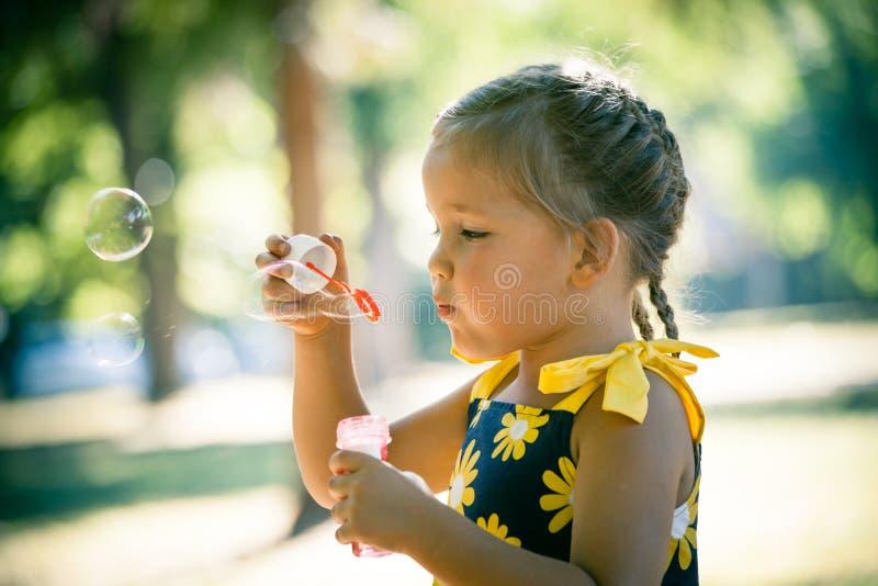 Meisjespel in van het de zeepbelsprofiel van de parkslag dichte omhooggaand stock foto
