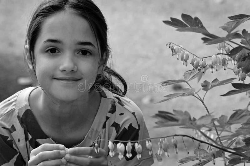 Meisjespelen met bloemen in een tuin royalty-vrije stock foto
